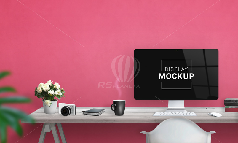 iMac computer display mockup on work desk with free space beside for promo text on rose color wall. Creative studio desk with coffee mug, plant, camera, keyboard, mouse and books